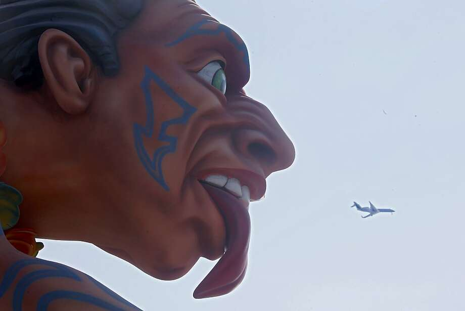"A plane flies across the scene as a float parades during the 129th edition of the Nice Carnival, Tuesday, Feb. 19, 2013, in Nice, southern France. The carnival celebrates the theme ""King of the 5 continents"". Photo: Lionel Cironneau, Associated Press"