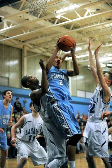 Columbia's Jahlil Nails goes in for a score during their Class AA boy's basketball playoff game agai