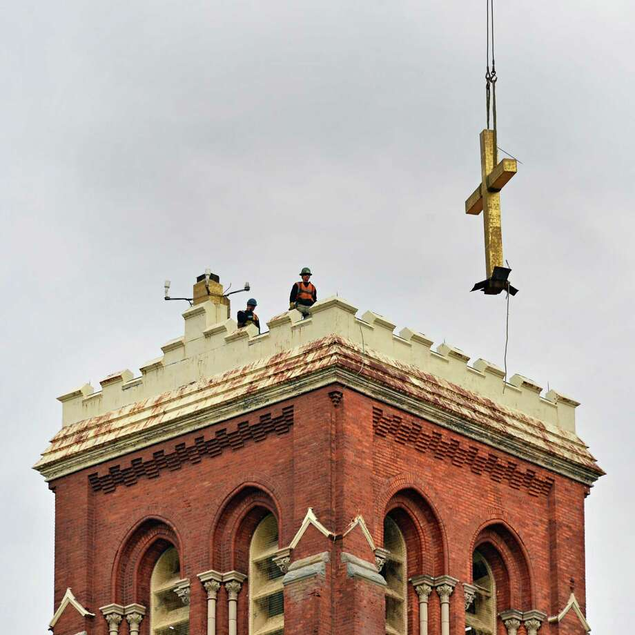 A workmen remove the cross atop the former St. Patrick's church in Watervliet Tuesday Feb. 19, 2013.  (John Carl D'Annibale / Times Union) Photo: John Carl D'Annibale