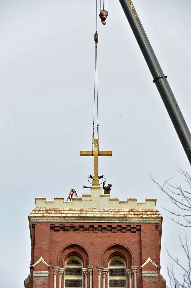 A worker prepares the cross atop the former St. Patrick's church in Watervliet for  removal Tuesday Feb. 19, 2013.  (John Carl D'Annibale / Times Union) Photo: John Carl D'Annibale