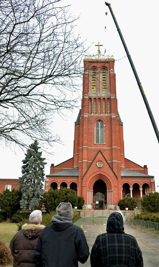 Neighbors watch as workers prepare to remove the cross atop the former St. Patrick's church in Watervliet Tuesday Feb. 19, 2013.  (John Carl D'Annibale / Times Union) Photo: John Carl D'Annibale