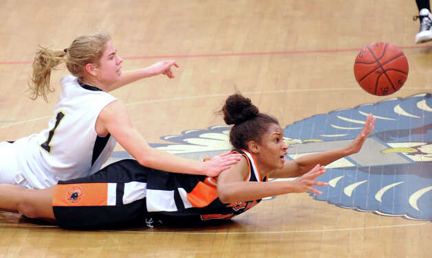 Stamford's Brianna Gordon, right, passes the ball to a teammate after beating Trumbull's Alexa Pfhol, left, to a loose-ball during the girls high school basketball FCIAC semifinal game between Stamford High School and Trumbull High School at Fairfield-Ludlowe High School, Tuesday, Feb. 19, 2013. Photo: Bob Luckey / Greenwich Time