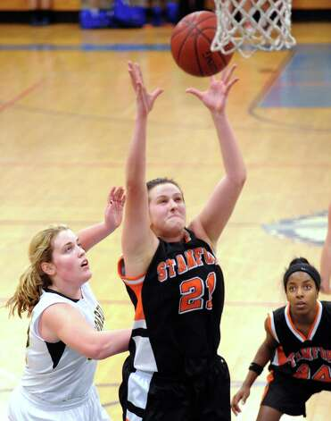 At center, Kelsey Santagata # 21 of Stamford rebounds the ball as Erin Moore of Trumbull, at left, looks on during the girls high school basketball FCIAC semifinal game between Stamford High School and Trumbull High School at Fairfield-Ludlowe High School, Tuesday, Feb. 19, 2013. Photo: Bob Luckey / Greenwich Time