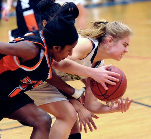 At left, Tiana England of Stamford goes a ball being controlled by Trumbull's Alexa Pfhol, right, during the girls high school basketball FCIAC semifinal game between Stamford High School and Trumbull High School at Fairfield-Ludlowe High School, Tuesday, Feb. 19, 2013. Photo: Bob Luckey / Greenwich Time