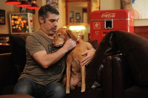 "Gary Dell'Abate's sits in his  ""man cave"" and  hugs his Murphy, his dog, in his house, Greenwich, Conn., Monday, Feb. 18, 2013. Gary Dell'Abate, the longtime Howard Stern sidekick and Old Greenwich resident, is co-host of a new VH1 Classic show on music and pop culture memorabilia called ""For What It's Worth."" Photo: Helen Neafsey / Greenwich Time"