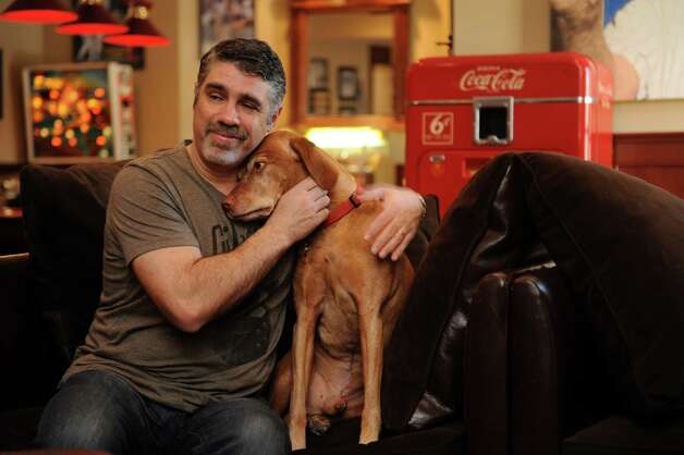 "Gary Dell'Abate's sits in his  ""man cave,"" and  hugs his Murphy, his dog, in his house, Greenwich, Conn., Monday, Feb. 18, 2013. Gary Dell'Abate, the longtime Howard Stern sidekick and Old Greenwich resident, is co-host of a new VH1 Classic show on music and pop culture memorabilia called ""For What It's Worth."" Photo: Helen Neafsey / Greenwich Time"