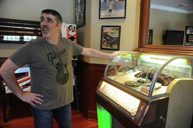 "Gary Dell'Abate stands by his jukebox in his ""man cave"" in his house, in Greenwich, Monday, Feb.18, 2013.  Dell'Abate, the longtime Howard Stern sidekick and Old Greenwich resident, is co-host of a new VH1 Classic show on music and pop culture memorabilia called ""For What It's Worth."" Photo: Helen Neafsey / Greenwich Time"