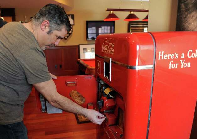 "Gary Dell'Abate shows where to insert coins in a 1950s-edition Coca-Cola machine that is part of his collection of pop culture memorabilia, in his Old Greenwich, Conn., home Monday, Feb. 18, 2013. Dell'Abate, the longtime Howard Stern sidekick and Old Greenwich resident, is co-host of a new VH1 Classic show on music and pop culture memorabilia called ""For What It's Worth."" Photo: Helen Neafsey / Greenwich Time"