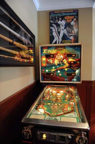 "Bally Eight Ball, Gary Dell'Abate's favorite pin ball game growing up, is part of his ""man cave"" in his Old Greenwich, Conn., home Monday, Feb. 18, 2013. Dell'Abate, the longtime Howard Stern sidekick and Old Greenwich resident, is co-host of a new VH1 Classic show on music and pop culture memorabilia called ""For What It's Worth."" Photo: Helen Neafsey / Greenwich Time"