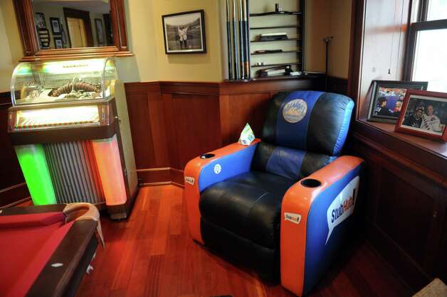"A leather recliner from the VIP seating area at Shea Stadium and a Rock-Ola Comet 120 jukebox highlight a trove of music and sports memorabilia owned by Gary Dell'Abate in his Old Greenwich, Conn., home. Dell'Abate, the longtime Howard Stern sidekick and Old Greenwich resident, is co-host of a new VH1 Classic show on music and pop culture memorabilia called ""For What It's Worth."" Photo: Helen Neafsey / Greenwich Time"