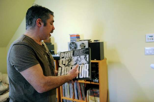 "Gary Dell'Abate looks at records in the attic in Greenwich, Conn., Monday, Feb. 18, 2013. Gary Dell'Abate, the longtime Howard Stern sidekick and Old Greenwich resident, is co-host of a new VH1 Classic show on music and pop culture memorabilia called ""For What It's Worth."" Photo: Helen Neafsey / Greenwich Time"
