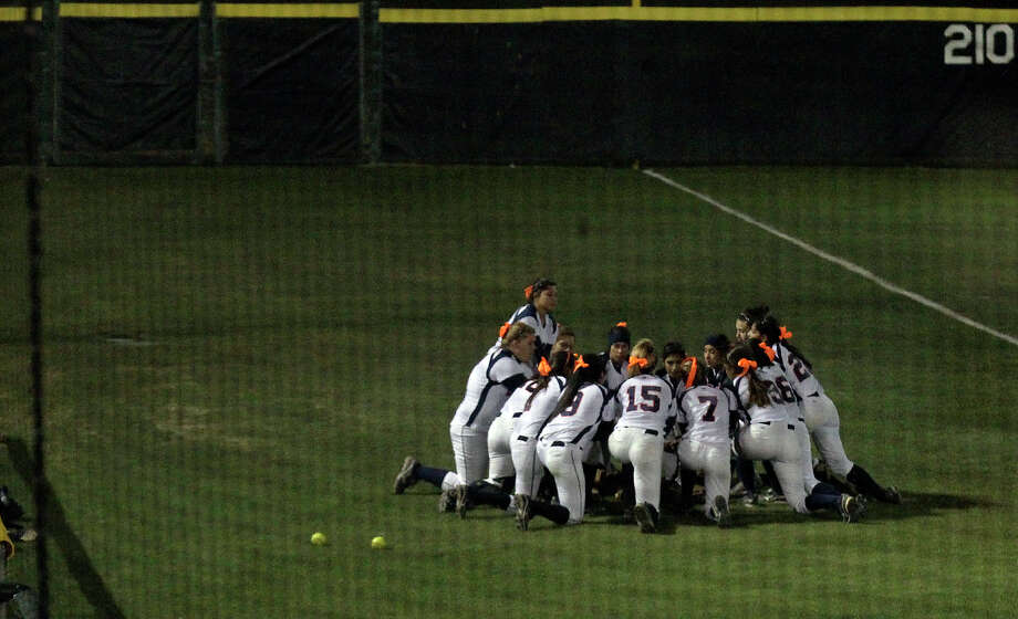 The Brandeis softball team gather in the outfield before their game against O'Connor on Tuesday, Feb. 19, 2013. The athletes wore orange ribbons with the initials of former teammate Gabriella Lerma who died in a drag racing incident on Tuesday, Feb. 19, 2013. Lerma was a junior at Brandeis. Photo: Kin Man Hui, San Antonio Express-News / © 2012 San Antonio Express-News