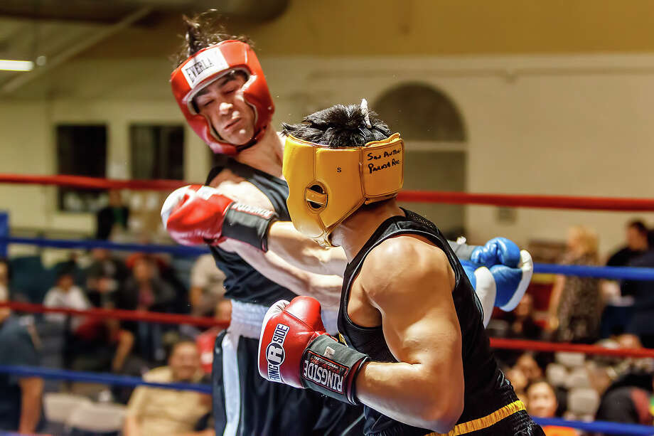 Mason Reina, boxing with San Antonio Parks and Recreation, ends his bout with Raging Bull Boxing's Lundberg Garrison with this shot to the head during their novice Welterweight bout on opening night of the 2013 San Antonio Regional Golden Gloves tournament at Woodlawn Gym on Tuesday, Feb. 19, 2013. Photo: Marvin Pfeiffer,  San Antonio Express-News / Express-News 2013