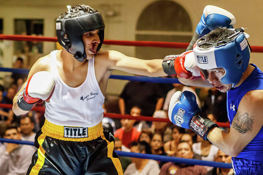 Jorge Maldanado (left) with Reyes Boxing School connects on a punch to Richard Garcia, boxing unattached, during their sub novice Lightweight bout on opening night of the 2013 San Antonio Regional Golden Gloves tournament at Woodlawn Gym on Tuesday, Feb. 19, 2013.  Maldanado came away with the decision in the bout. Photo: Marvin Pfeiffer,  San Antonio Express-News / Express-News 2013