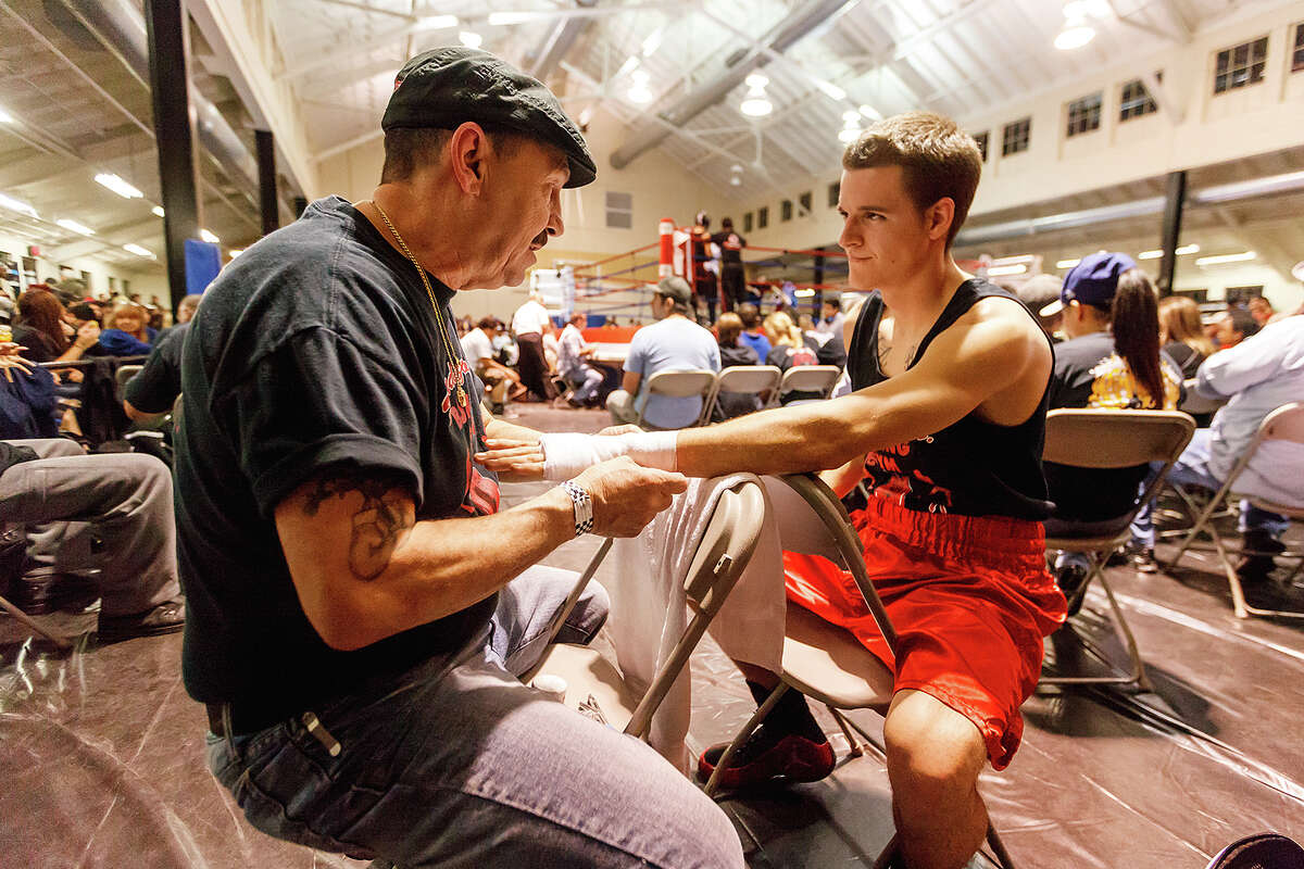Cassidy Allison (right), fighting with Randazzo Brothers Boxing Club, gets his hands wrapped prior to his bout by Santo Randazzo prior to his bout on opening night of the 2013 San Antonio Regional Golden Gloves tournament at Woodlawn Gym on Tuesday, Feb. 19, 2013.