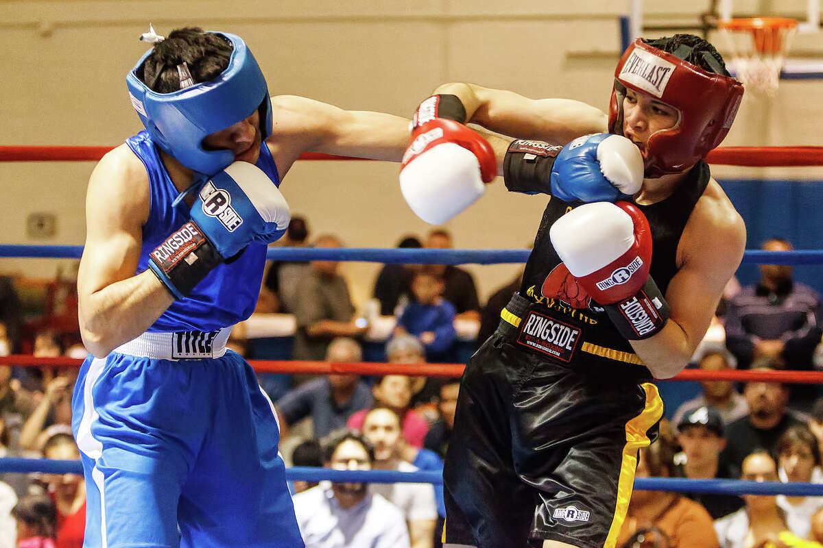 Julio Casasola (left), with Casasola Boxing Club, lands a punch on Cresencio Ramos with San Antonio Parks and Recreation during their open Lightweight bout on opening night of the 2013 San Antonio Regional Golden Gloves tournament at Woodlawn Gym on Tuesday, Feb. 19, 2013. Ramos, however, came away with the decision.