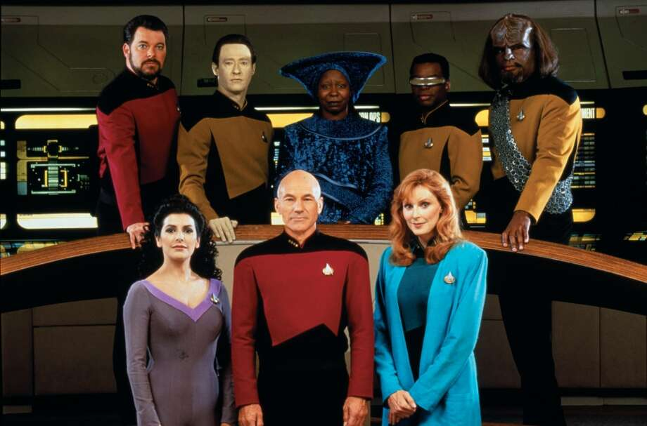 The ol' TNG Enterprise crew in 1987, played by (left to right, front to back): Marina Sirtis, Patrick Stewart and Gates McFadden, Jonathan Frakes, Brent Spiner, Whoopi Goldberg, LeVar Burton and Michael Dorn.