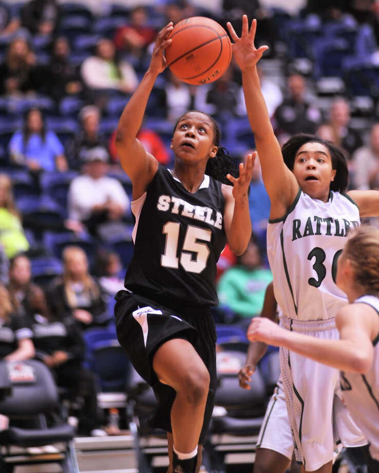 Steele's Kyra Lambert drives for a layup over the outstretched hand of Reagan's Briana Gladney during their 5A playoff clash Tuesday. Photo: Robin Jerstad, Robin Jerstad, For The Express-News