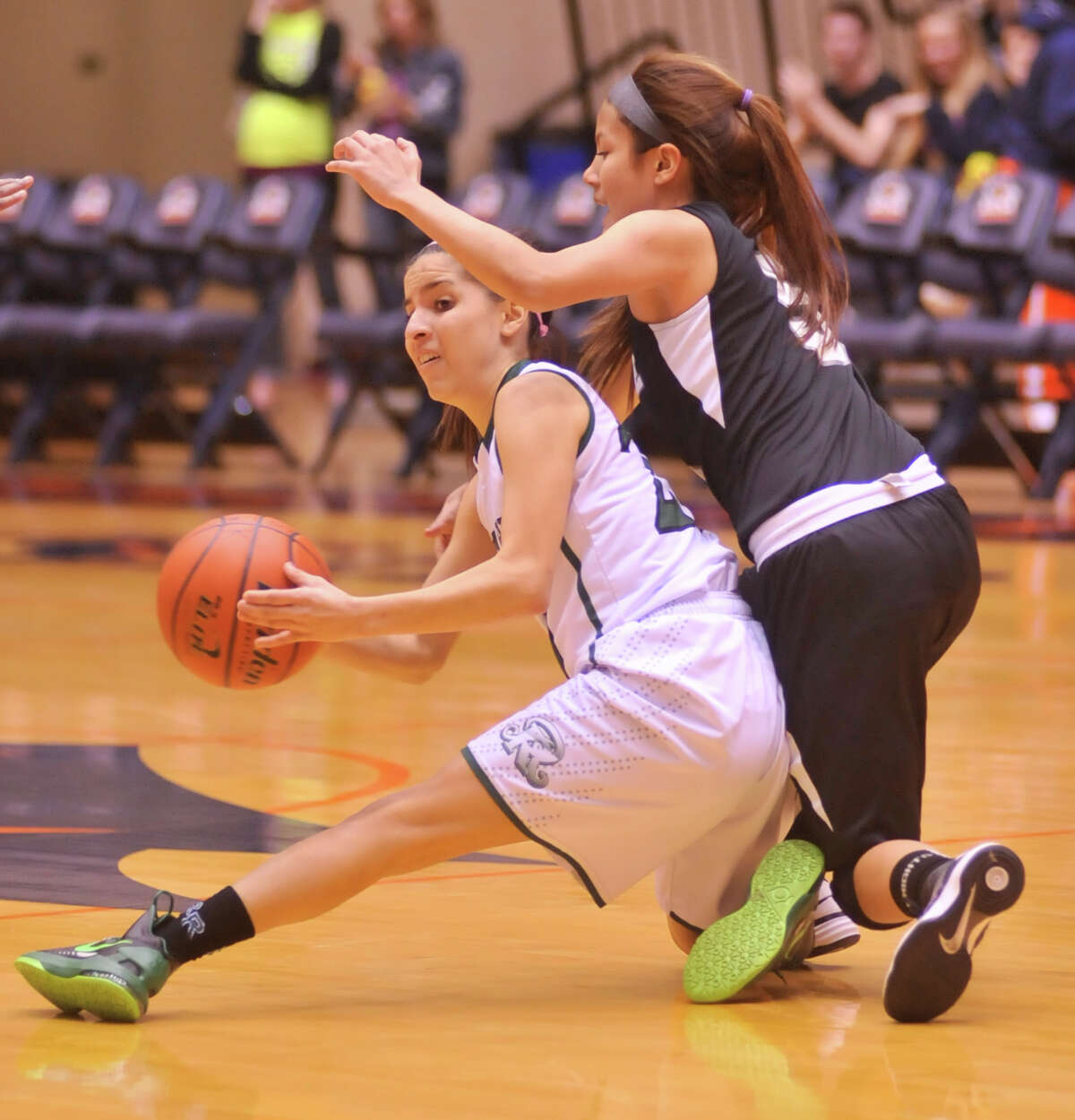 Reagan's Tessa Ramirez is looks to pass from the floor as Steele's Sarai defends during their 5A playoff game Tuesday, Feb. 19, 2013.