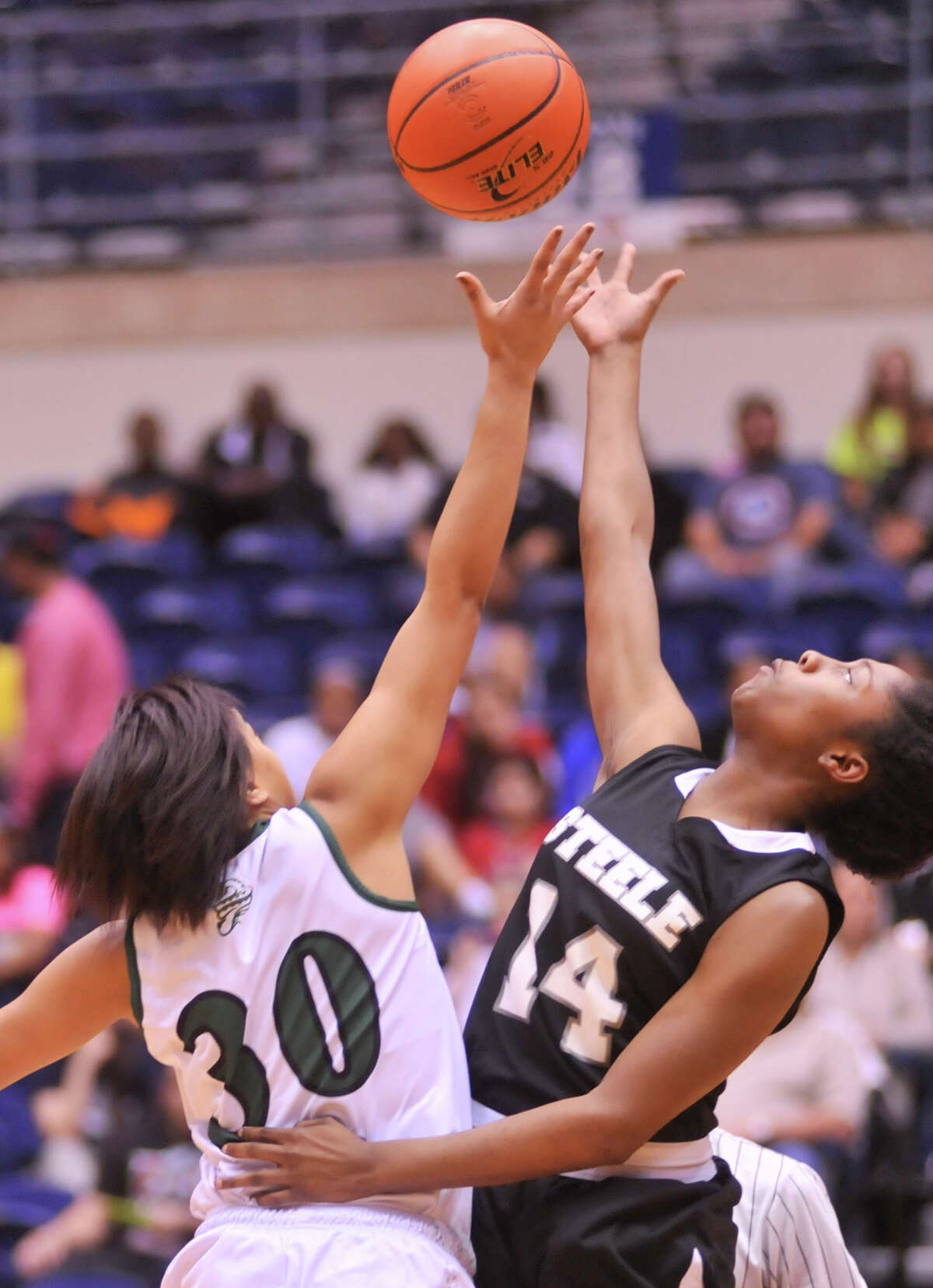 Reagan's Briana Gladney (30) and Steele's McKenzie Calvery (14) battle for control of the open tip during their 5A playoff game Tuesday, Feb. 19, 2013.