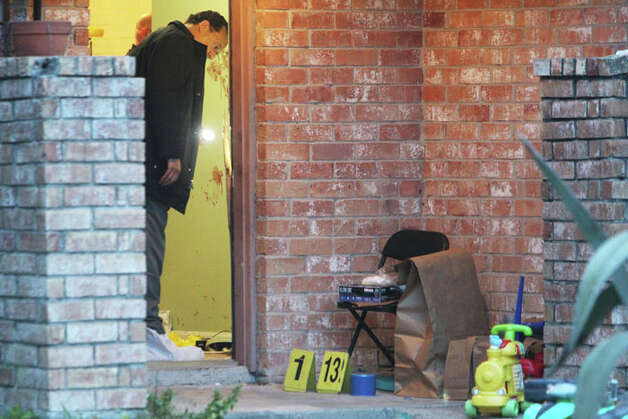 A Harris County sheriff's investigator inspects the entry of a home where three suspects allegedly stabbed a man to death Tuesday night in the 13200 block of Benford Drive. (Mayra Beltran / Houston Chronicle) Photo: .