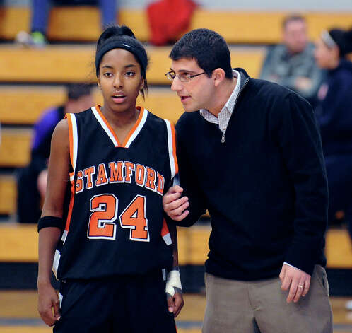 At left, Tiana England # 24 of Stamford listens to her coach Todd Parness during the girls high school basketball FCIAC semifinal game between Stamford High School and Trumbull High School at Fairfield-Ludlowe High School, Tuesday, Feb. 19, 2013. Photo: Bob Luckey / Greenwich Time
