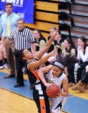 At left, Brianna Gordon of Stamford covers Joyce Woolen of Trumbull during the girls high school basketball FCIAC semifinal game between Stamford High School and Trumbull High School at Fairfield-Ludlowe High School, Tuesday, Feb. 19, 2013. Photo: Bob Luckey / Greenwich Time