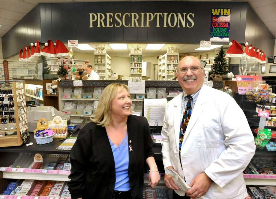 Long time English Drug employee, Carolyn Hatzi, left, stands with Dan Boulanger inside the Bethel business, on Monday, Dec.21,2009. Photo: Michael Duffy / The News-Times