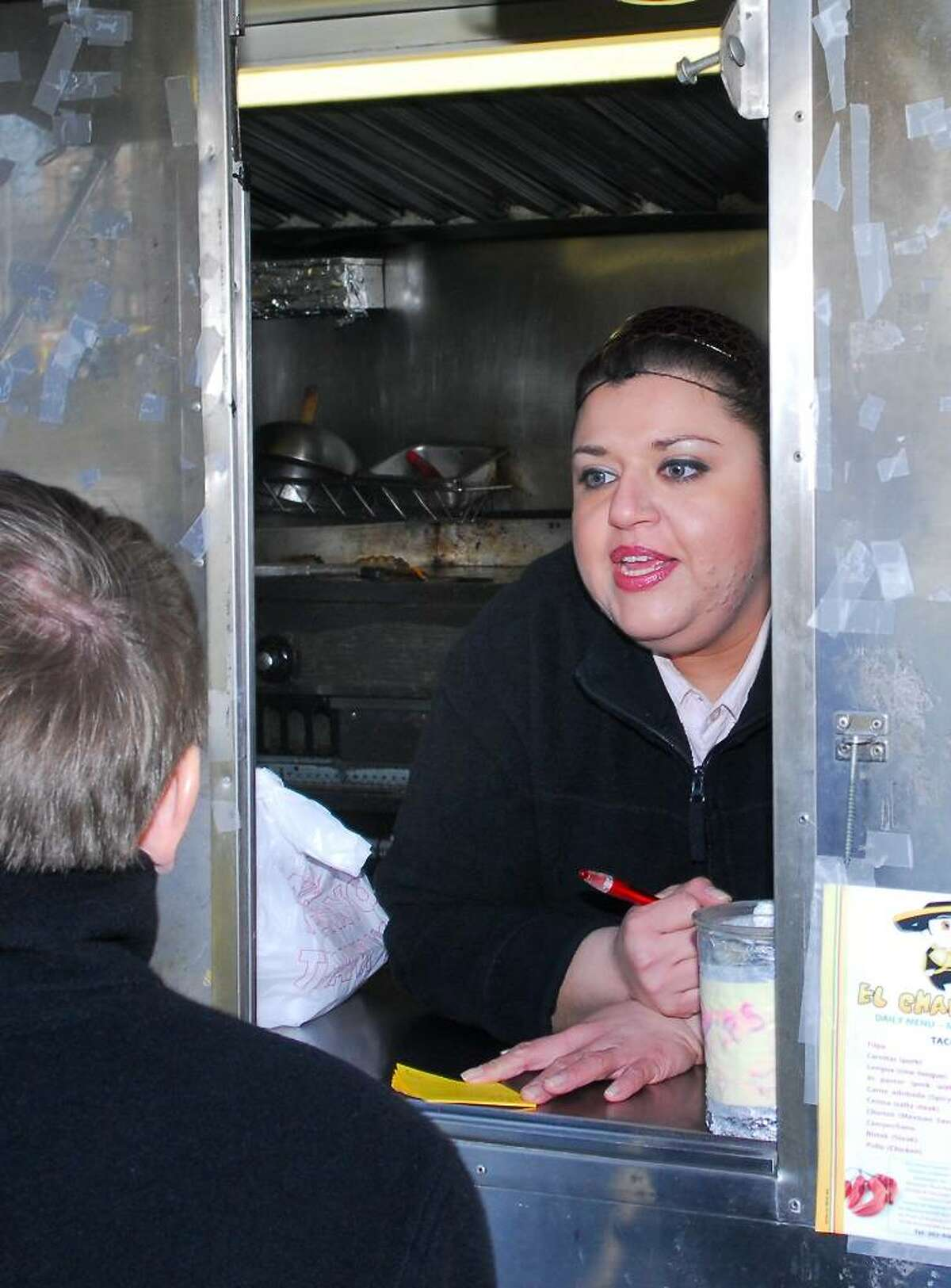 Alex Terron, a proprietor of El Charrito takes an order inside her truck parked on Richmond Place in Stamford on Tuesday Dec. 29th, 2009.