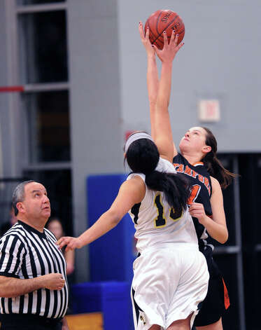At right, Kelsey Santagata # 21 of Stamford jumps center against Trumbull's Joyce Woolen # 13 during the start of the girls high school basketball FCIAC semifinal game between Stamford High School and Trumbull High School at Fairfield-Ludlowe High School, Tuesday, Feb. 19, 2013. Photo: Bob Luckey / Greenwich Time