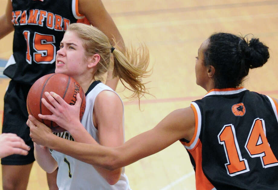 At left, Alexa Pfhol of Trumbull is defended by Brianna Gordon # 14 of Stamford during the girls high school basketball FCIAC semifinal game between Stamford High School and Trumbull High School at Fairfield-Ludlowe High School, Tuesday, Feb. 19, 2013. Photo: Bob Luckey / Greenwich Time