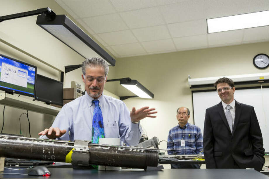 John Maida, left, talks about fiber optic sensor technology attached to well casing during a tour of Halliburton's Fiber Optics Facility in Houston.