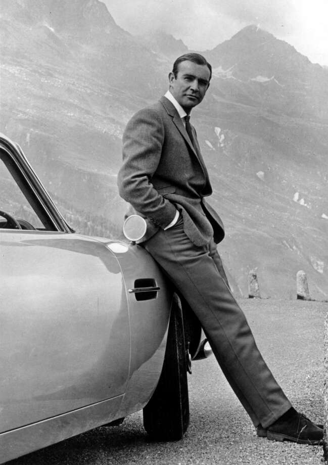 Actor Sean Connery poses as James bond next to his Aston Martin DB5 in a scene from the United Artists release 'Goldfinger' in 1964. Photo: Michael Ochs Archives, Getty Images / Michael Ochs Archives