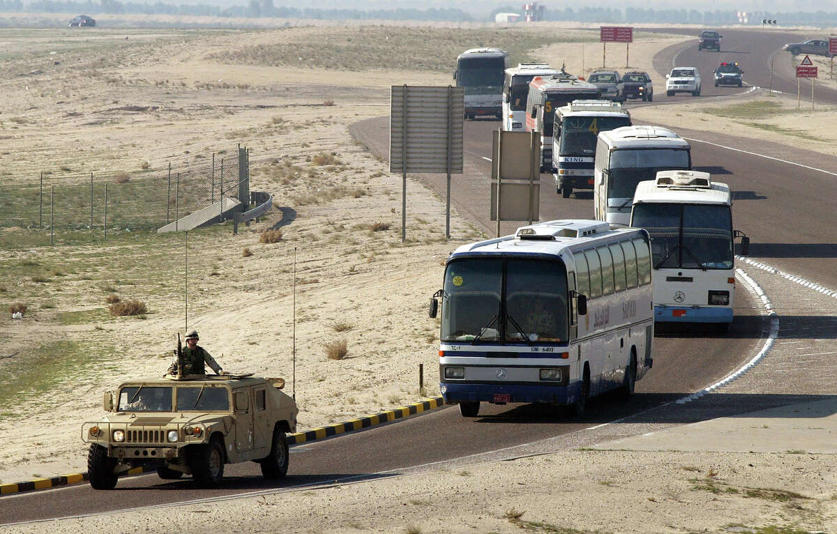 A U.S. Army Humvee escorts civilian buses loaded with U.S. soldiers from the International Airport January 10, 2003 in Kuwait City. The United States continues a low key influx of troops in the biggest military buildup in the region since the Gulf War.