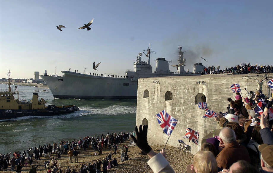 Members of the public line the shore as the aircraft carrier HMS Ark Royal leaves her base January 11 in Portsmouth, England, were she will lead a Naval Task Group to the Mediterranean. Ark Royal will fly the flag of the Commander UK Maritime Forces Rear Admiral David Snelson and it is widely beleived that the ship would take part in any military action against Iraq. Photo: Julian Herbert, Getty Images / 2003 Getty Images