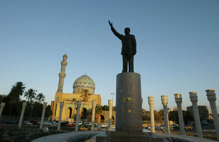 A monument to Iraqi President Saddam Hussein stands with a mosque in the background February 1, 2003 in Baghdad. As U.S. President George W. Bush continues to press his case for a pre-emptive war on Iraq, Chief U.N. weapons inspector Hans Blix scheduled a trip to Baghdad for February 8 to meet with Iraqi officials about disarmament. Photo: Oleg Nikishin, Getty Images / 2003 Getty Images