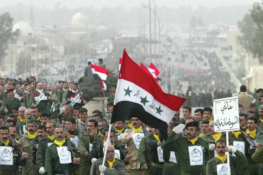 Iraqi men participate during a march in defiance of U.S. threats to invade Iraq February 4, 2003 in
