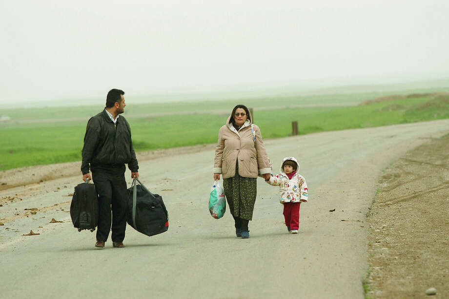 A father from Baghdad is fleeing Iraq at the Qoshtapa  checkpoint near Erbil with his preganant wife and daughter. Imminent war has created a constant stream of refugees into Northern Iraq in the face of an attack by Iraq. Photo: Patrick Barth, Getty Images / 2003 Getty Images