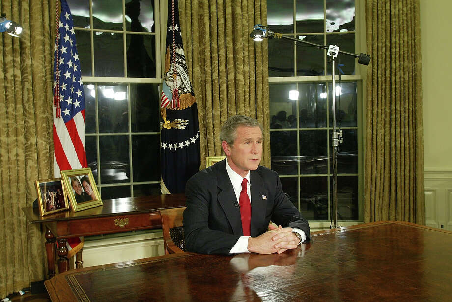 "U.S. President George W. Bush  addresses the nation March 19, 2003 in the Oval Office of the White House in Washington, DC. Bush announced that the U.S. military struck at ""targets of opportunity"" in Iraq March 19, 2003 in Washington, DC. Air defense sirens and anti-aircraft fire was reported briefly in Baghdad. Photo: Alex Wong, Getty Images / Getty Images"
