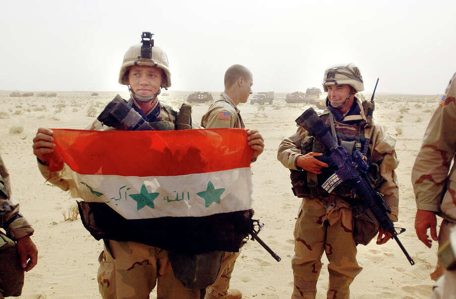 U.S. Army 3rd Infantry Division 3-7 infantry Corporal Charles Johnson, from Myrtle Beach, South Carolina, shows his squad an Iraqi flag captured during an raid on a Iraqi border post late the day before March 21, 2003. U.S. and British forces are currently assaulting Iraq from land, sea and air in what has been dubbed Operation Iraqi Freedom. Photo: Scott Nelson, Getty Images / 2003 Getty Images