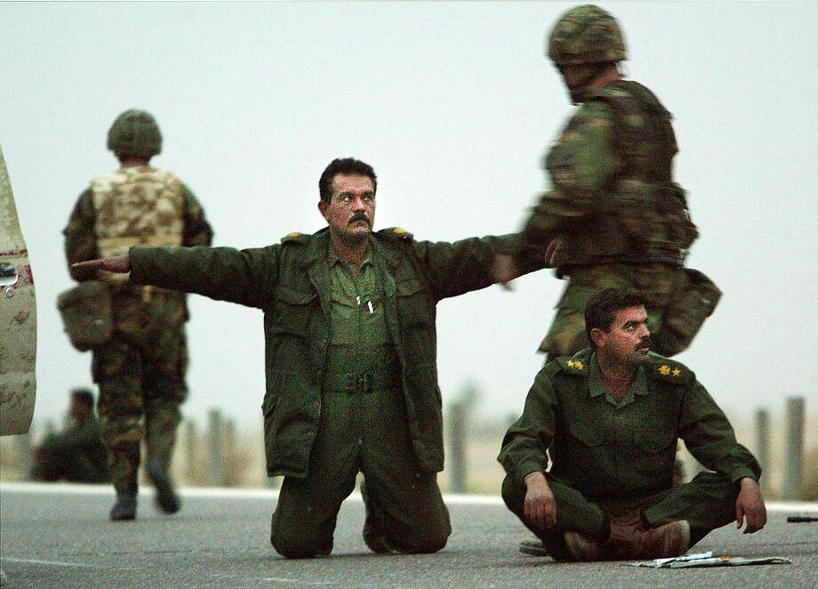 Iraqi troops surrender themselves to U.S. Marines March 21, 2003 in Safwan, Iraq.  Chaos reigned in southern Iraq March 21, as coalition troops continued their offensive to remove Iraqi president Saddam Hussein. Photo: Chris Hondros, Getty Images / 2003 Getty Images