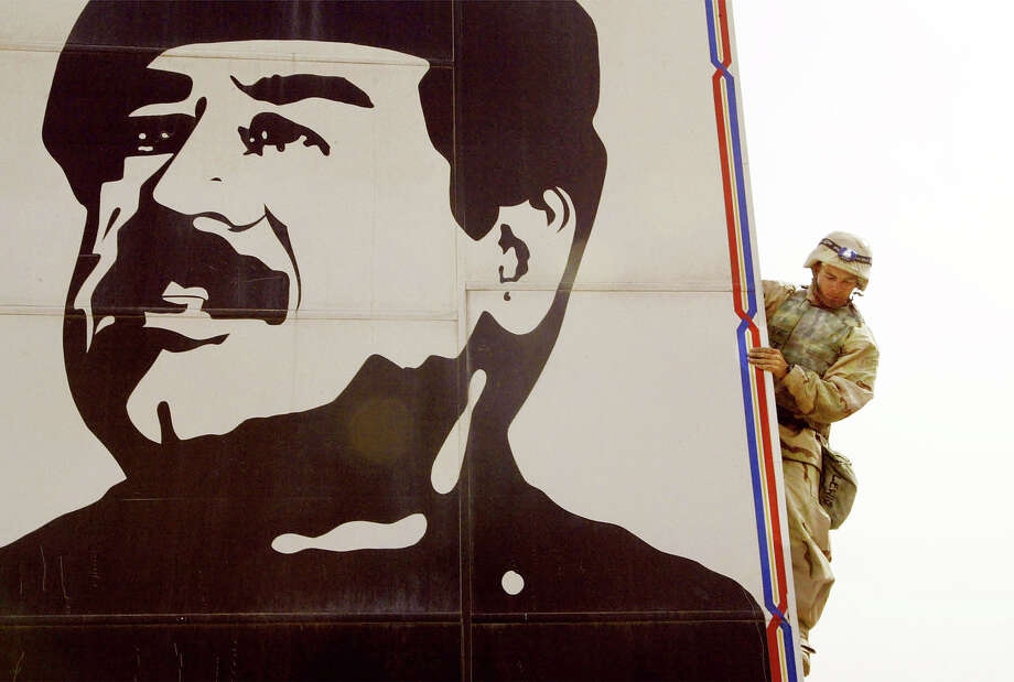 A U.S. Marine attached  a cable to pulls down a billboard of Saddam Hussein March 21, 2003 in Safwan, Iraq.  Chaos reigned in southern Iraq as coalition troops continued their offensive to remove Iraq's leader from power. Photo: Chris Hondros, Getty Images / 2003 Getty Images