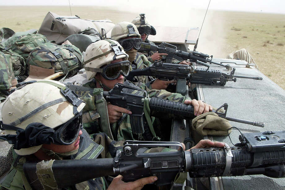 U.S. Marines  from Task Force Tarawa keep an eye out for enemy forces in an armored attack vehicle as they roll through the Iraqi countryside March 21, 2003 on their way to an objective in Iraq.  U.S. and British troops encountered both hostile fire and surrendering Iraqis as they pushed north into Iraq. Photo: Joe Raedle, Getty Images / 2003 Getty Images