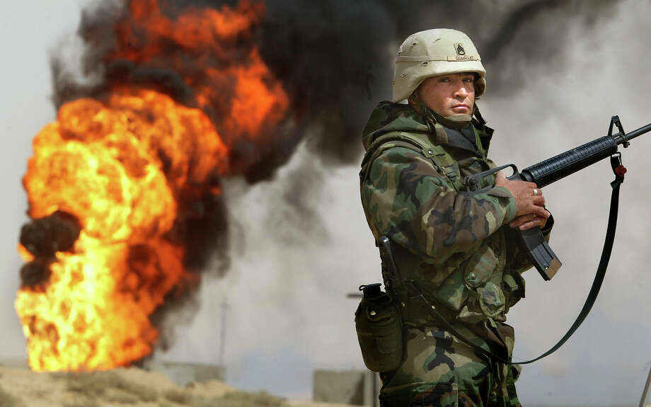 U.S. Army Staff Sergeant Robert Dominguez, of Mathis, Texas, stands guard next to a burning oil well at the Rumayla oil fields March 27, 2003 in Rumayla, Iraq. Several oil wells were set ablaze by retreating Iraqi troops in the Ramayla area, the second largest offshore oilfield in the country, near the Kuwaiti border. Photo: Mario Tama, Getty Images / 2003 Getty Image