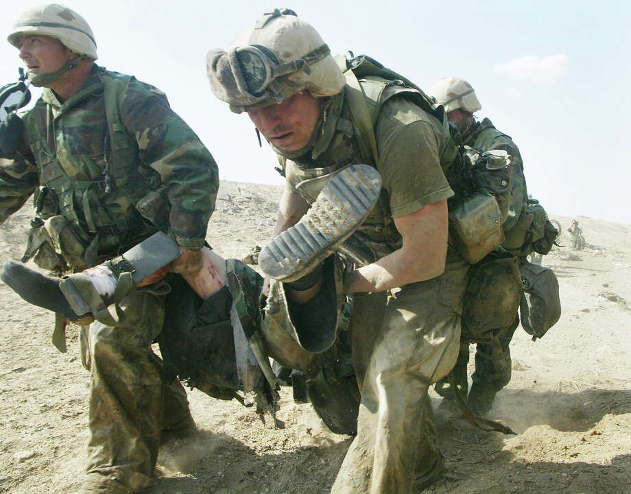 U.S. Marines from Task Force Tarawa carry a wounded Marine during a gun battle March 23, 2003 in the southern Iraqi city of Nasiriyah. The Marines suffered a number of deaths and casualties during gun battles throughout the city. Photo: Joe Raedle, Getty Images / 2003 Getty Images