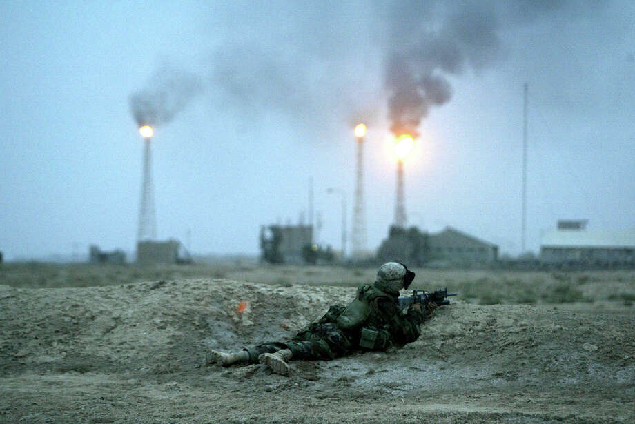A Marine from the 1st Marine Division takes fire from Iraqi Army stragglers near Basra's main oil refinery March 21, 2003 25 km south of Basra, Iraq.  A coalition led by US forces attacked Iraq today. Photo: Robert Nickelsberg, Getty Images / Robert Nickelsberg