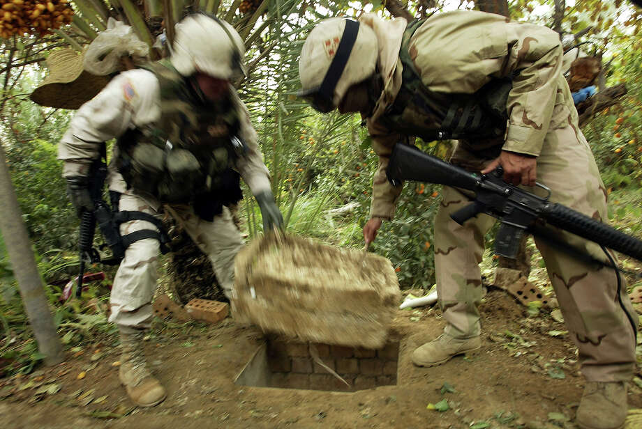 "American soldiers remove a Styrofoam cover that plugged up the ""spider hole"" where Saddam Hussein hiding when he was captured December 15, 2003 in Ad Dawr, Iraq.  Iraq's notorious dictator was captured in a raid at the compound on December 13. Photo: Chris Hondros, Getty Images / 2003 Getty Images"