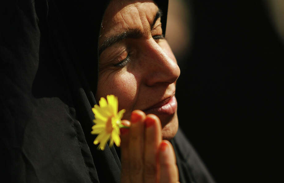 An Iraqi woman pauses for a moment at a rally on March 8, 2004 in Baghdad, Iraq. Dozens of women, mostly dressed in traditional clothing are protesting about women's rights into the make-up of the new government. Photo: Spencer Platt, Getty Images / 2004 Getty Images