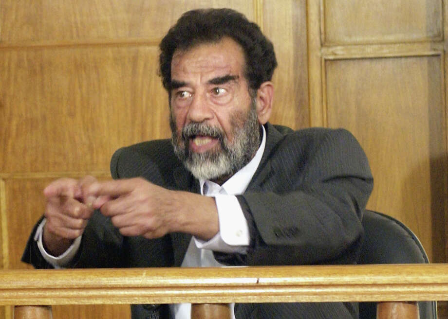 Former Iraqi President Saddam Hussein reacts as a list of charges that he and 11 other high level defendents will face is read in an Iraqi courtroom on July 1, 2004 in Baghdad, Iraq.  Hussein was transferred into the legal custody of Iraqi authorities on June 30, 2004 but remains in the physical custody of the U.S. Military at an undisclosed location. Hussein is not expected to face trial in an Iraqi court for at least several months. Photo: Pool, Getty Images / 2004 Getty Images