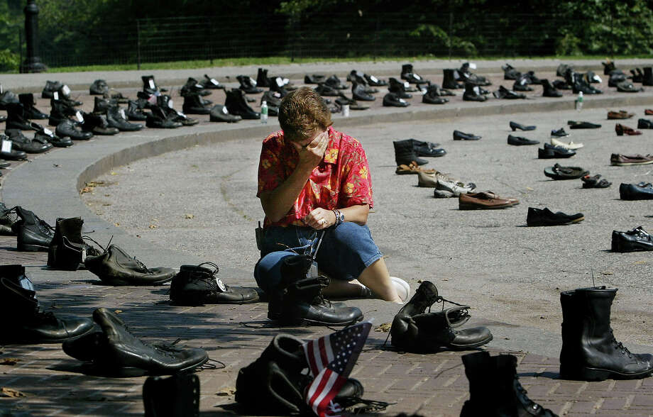 Sue Niederer of Pennington, New Jersey grieves over a memorial representing her son, Seth Dvorin, who was killed in Iraq earlier this year, August 28, 2004 in Central Park in New York. The exhibit, called Eyes Wide Open, was created by the pacifist American Friends Service committee and includes a pair of boots for every U.S. soldier killed in Iraq. Photo: Chris Hondros, Getty Images / 2004 Getty Images